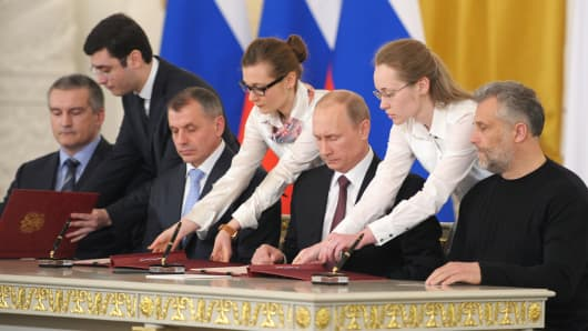 Russia's President Vladimir Putin (2nd R), Crimean Prime Minister Sergei Aksyonov (L), Crimean parliament speaker Vladimir Konstantionov (2nd L) and Alexei Chaly, Sevastopol's new de facto mayor (R), sign a treaty on the Ukrainian Black Sea peninsula becoming part of Russia, in the Kremlin, Moscow, March 18, 2014.
