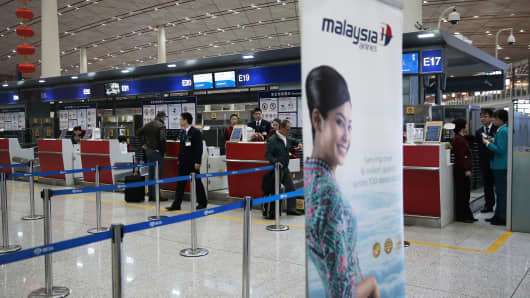 Passengers check-in at Malaysia Airlines in Beijing, China.