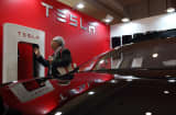 An attendee looking at a battery charger is reflected on a Tesla Motors Inc. Model S electric vehicle.