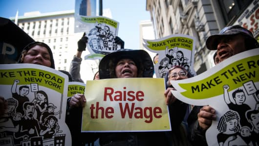 Women hold banners during a protest for higher wages for fast food workers on March 18, 2014 in New York City.