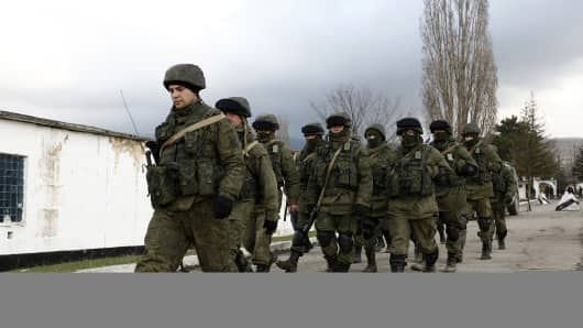 Russian armed forces stand guard around the Ukrainian military base in the village of Perevalne, 20 km south of Simferopol.