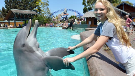 Danielle Bradbery meets a bottlenose dolphin during a visit to SeaWorld San Diego, August 16, 2013.