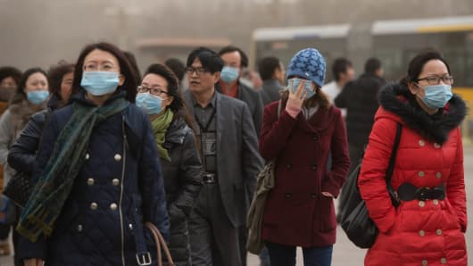 People wearing face masks walk near the Forbidden City during heavy pollution in Beijing on February 28, 2013.