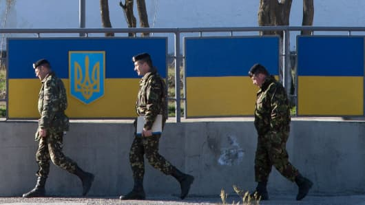 Russian officers walk past the Ukrainian marine battalion headquarters in the Crimean city of Feodosia