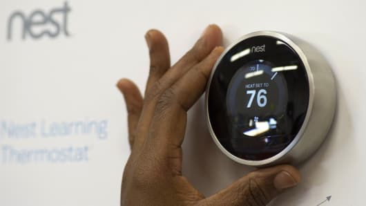 A customer checks a Nest Labs Inc. digital thermostat on display at a Home Depot Inc. store in Emeryville, California.