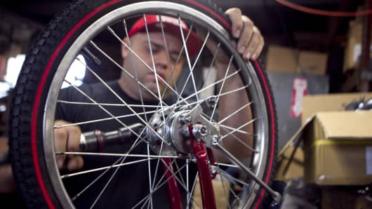 An employee assembles front-end brakes to a bicycle frame at Worksman Cycles in Queens, New York.