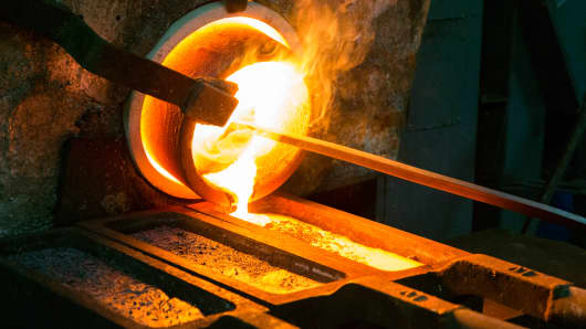 Molten gold pours from a furnace during the final stage of the refining process.