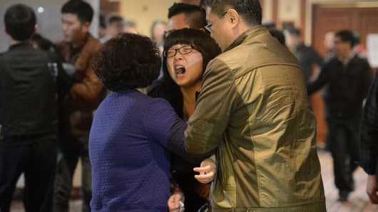 Grieving relatives of passengers on Malaysia Airlines flight MH370 leave a hotel hall at after being told the news that the plane plunged into Indian Ocean in Beijing.
