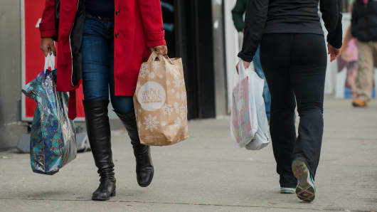 edestrians carry shopping bags while walking in the Harlem neighborhood of New York.
