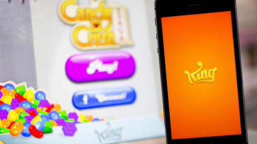 The King Digital Entertainment Plc logo and 'Candy Crush Saga' game are displayed on an Apple iPhone 5s and iPad Air in this arranged photograph.