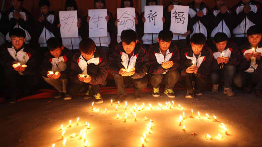 High school students hold candles during a vigil for passengers of the missing Malaysia Airline flight MH370 in Lianyungang, east China's Jiangsu province.