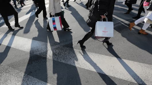 Pedestrians carry shopping bags while crossing an intersection in the Ginza district of Tokyo, Japan.