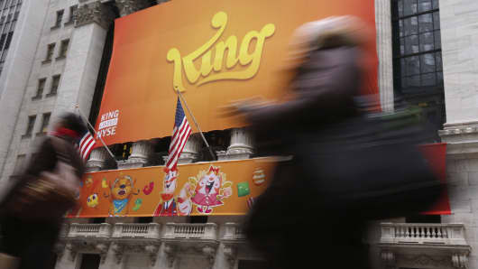 Pedestrians walk past a King Digital Entertainment Plc banner hanging on the facade of the New York Stock Exchange (NYSE) in New York.