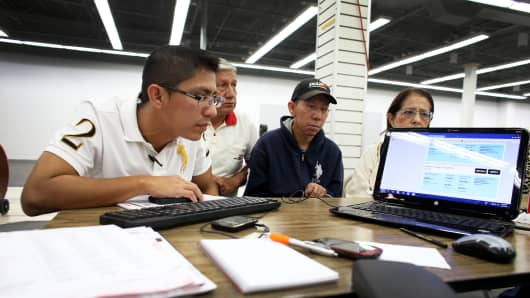 People check health insurance plans under the Affordable Care Act at the Mall of the Americas on March 20, 2014, in Miami.