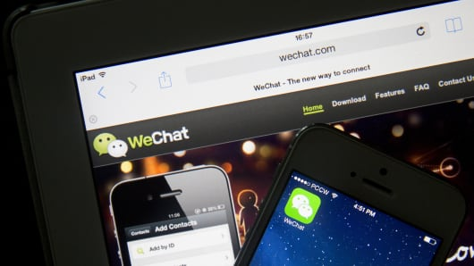 The Tencent Holdings Ltd.'s WeChat application icon and website are displayed on an Apple Inc. iPhone 5s, right, and Apple Inc. iPad respectively in an arranged photograph in Hong Kong, China.