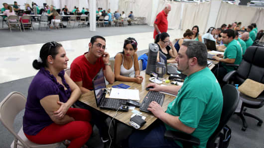 Customers sit with an insurance agent from Sunshine Life and Health Advisors as they and others try to purchase health insurance under the Affordable Care Act at a store setup in the Mall of the Americas on March 20, 2014, in Miami.