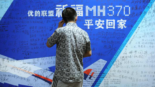 A man looks at a billboard in support of missing Malaysia Airlines flight MH370 while relatives attend a meeting with delegates from Malaysia at the Metro Park Lido Hotel in Beijing.