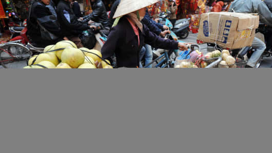 A vendor hawks fruits along a street in downtown Hanoi