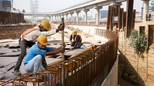 Workers at a construction site below an elevated track, operated by Rapid MetroRail Gurgaon, in Gurgaon, India, in March 2014.
