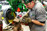 A service technician grinds temporary spot welds while working on an exhaust manifold for a John Deere tractor at Klein Equipment, a John Deere dealership, in Galesburg, Illinois.
