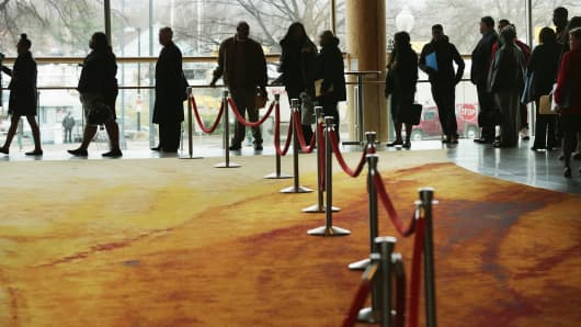 People seeking employment wait in line to enter a job fair at the Arena Stage at the Mead Center for American Theater March 28, 2014 in Washington.