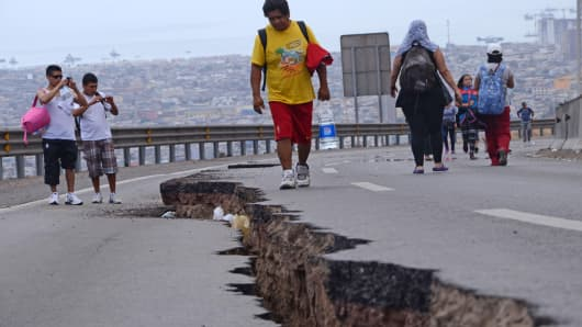 People walk along a cracked road in Iquique, northern Chile, on April 2, 2014 after a powerful 8.2-magnitude earthquake hit off Chile's Pacific coast.