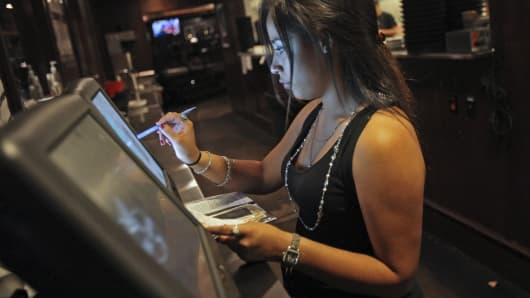 A waitress prepares a patron's bill at the Bar Louie restaurant located in the River North neighborhood of Chicago.
