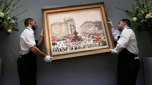 Sotheby's employees re-hang LS Lowry's painting 'Piccadilly Circus, in London, on March 21, 2014.