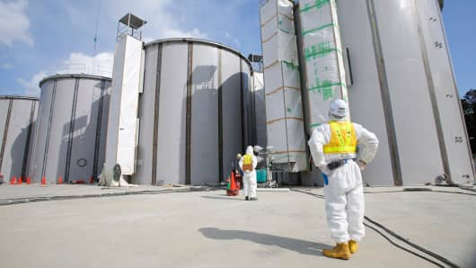 A worker wearing a protective suit looks at storage tanks for radioactive water under construction in the J-1 area at Tokyo Electric Power Co.'s Fukushima Dai-Ichi nuclear power plant in Fukushima, Japan, March 10, 2014.
