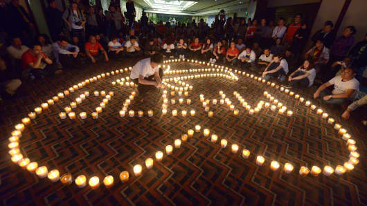 A woman (C) lights a candle as Chinese relatives of passengers on the missing Malaysia Airlines flight MH370 take part in a prayer service at the Metro Park Hotel in Beijing.