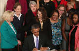 President Barack Obama is flanked by Lilly Ledbetter (L) and other women while signing an executive order banning federal contractors from retaliating against employees during an event in the East Room of the White House in honor of 'Equal Pay Day' on April 8, 2014 in Was