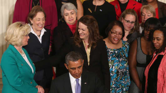 President Barack Obama is flanked by Lilly Ledbetter (L) and other women while signing an executive order banning federal contractors from retaliating against employees during an event in the East Room of the White House in honor of 'Equal Pay Day' on April 8, 2014 in Washington, DC.