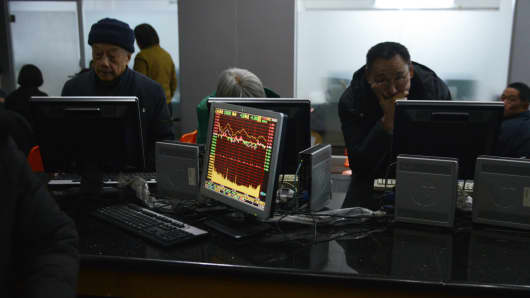 Investors looking at stock prices on screens in a securities exchange in Shanghai.