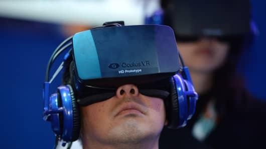 "An attendee wears an Oculus Rift HD virtual reality head-mounted display as he plays ""EVE: Valkyrie,"" a multiplayer virtual reality dogfighting shooter game, at the Intel booth at the 2014 International CES in Las Vegas."