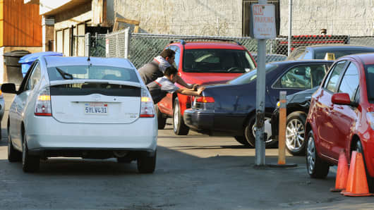 Toyota mechanics push a car next to a Prius hybrid model in the service area of a Toyota dealership in Santa Monica, Calif.