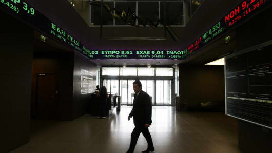 Stock Exchange displays show stock price movements in Athens, Greece.