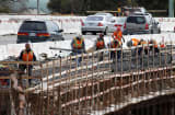 Construction crews work on a freeway overpass along Highway 101 in Novato, California.
