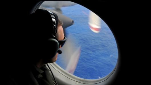A crew member of a Royal New Zealand Airforce (RNZAF) P-3K2-Orion aircraft helps to look for objects during the search for missing Malaysia Airlines flight MH370 in flight over the Indian Ocean off the coast of Perth, Australia.