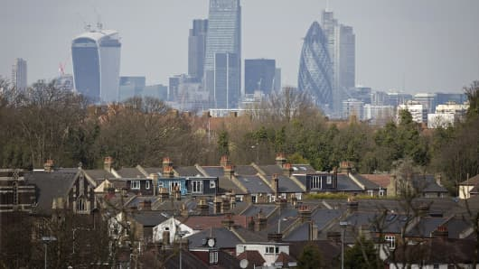 Skyscrapers  stand on the horizon beyond rows of residential houses in London, U.K.