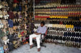 A shoe salesman sits writing as he waits for customers at a store in the Brigade Road shopping area in central Bangalore, India.