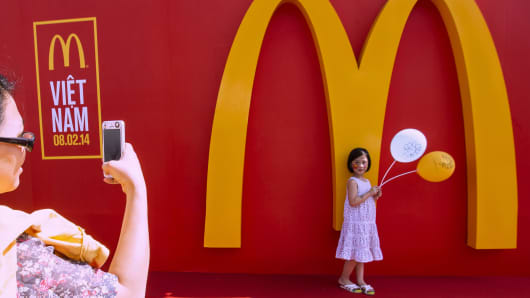 A mother takes picture of her daughter in front of the company's logo during the opening ceremony of the country's first McDonald's restaurant in Ho Chi Minh city on February 8, 2014.