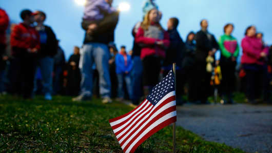 An American flag sits stuck in the grass during a candlelight vigil for the one-year anniversary of the Boston Marathon bombings at Garvey Park on April 15, 2014 in Boston, Massachusetts.