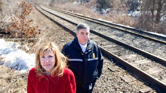 Joseph Targ, right, and Jodi Ross, respectively the fire chief and town manager of Westford, Mass., revisit the site where a train carrying natural gas recently derailed, on March 24, 2014.