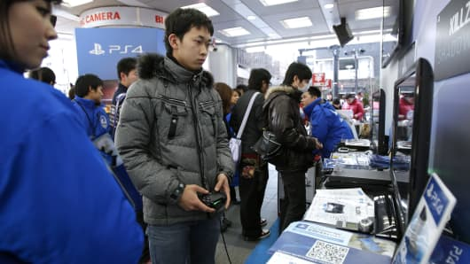 A customer, second from left, plays a video game on a Sony Computer Entertainment Inc. PlayStation 4 (PS4) video game console at a Bic Camera Inc. electronics store in Tokyo, Japan.