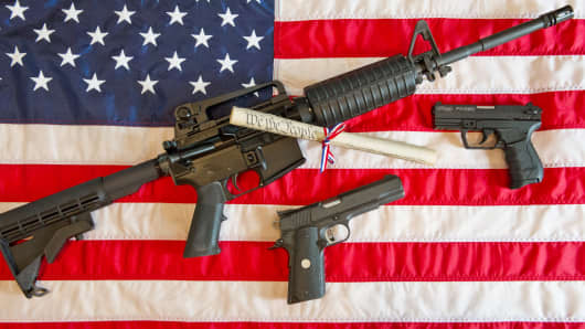 A Colt AR-15 semi-automatic rifle, a Colt .45 semi-auto handgun and a Walther PK380 semi-auto handgun and a copy of the US Constitution on top of an American flag.