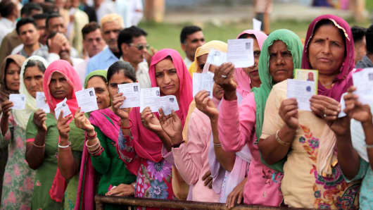 Voters showing their ID cards as they stand in a queue to cast their votes at a polling station on April 17, 2014 in Jammu, India.