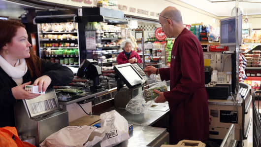 A clerk rings up a customer at Cal-Mart Grocery on March 27, 20