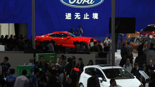 Visitors check out Ford cars on display at the China International Exhibition Center new venue during the 'Auto China 2014' Beijing International Automotive Exhibition in Beijing.