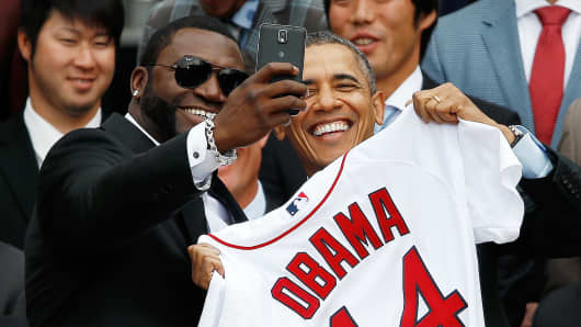 Boston Red Sox designated hitter David Ortiz (L) poses for a 'selfie' with President Barack Obama during a ceremony on the South Lawn of the White House to honor the 2013 World Series champion Boston Red Sox on April 1, 2014.