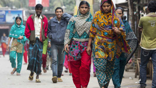 Garment factory workers walk along a road during their lunch break in the Savar district of Dhaka, Bangladesh.